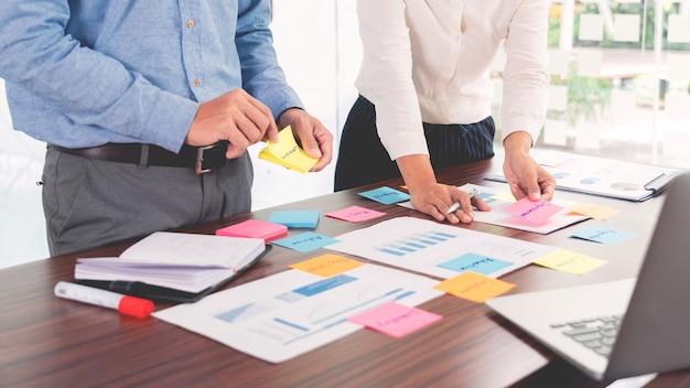 El empresario pega notas coloridas para la lluvia de ideas sobre la mesa trabajando en un nuevo proyecto para compartir la idea