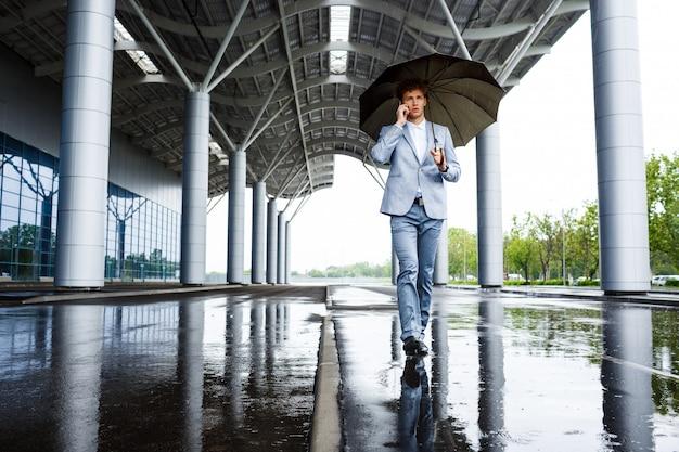 Empresario pelirrojo con paraguas hablando por teléfono