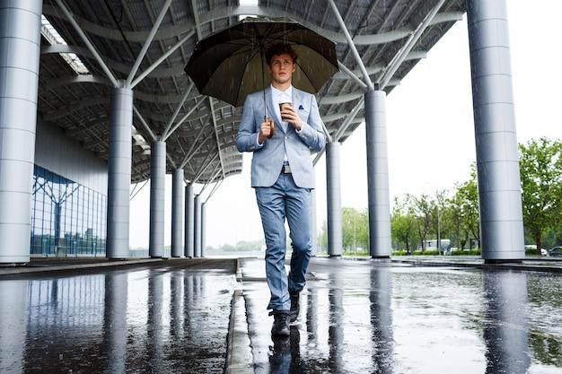 Empresario pelirrojo con paraguas tomando café