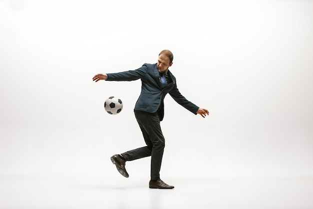 Empresario con pelota de fútbol en la oficina