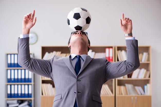 Empresario con pelota de futbol en la oficina