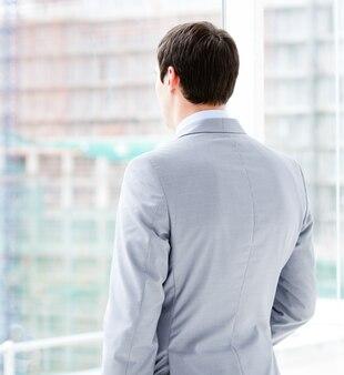 Empresario de pensamiento mirando por la ventana