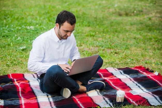Empresario pensativo en el campo. con laptop