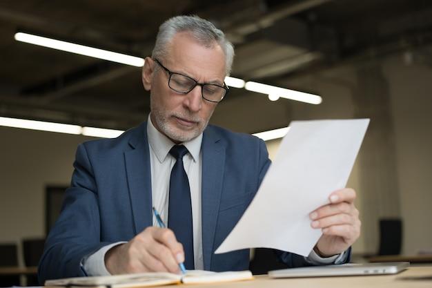 Empresario pensativo escribiendo notas, sosteniendo documentos sentado en la oficina moderna