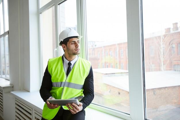 Empresario pensativo en sitio de construcción