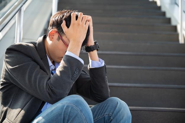 Empresario perdido en la depresión sentado en las escaleras sufriendo dolor emocional tristeza