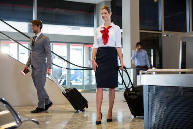 Empresario y personal femenino caminando con equipaje en la sala de espera