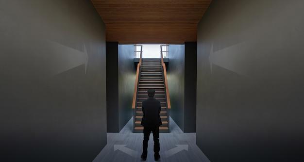 Empresario de pie cerca de la flecha en la pared negra y la escalera, el concepto de lograr su éxito