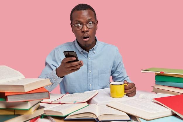 Empresario de piel oscura sostiene el teléfono móvil en una mano y una taza de café en la otra, vestido con ropa formal