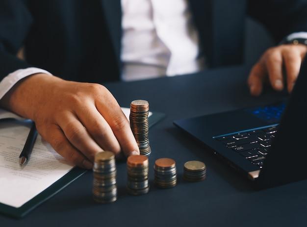 Empresario con pila de monedas usando una computadora portátil para calcular