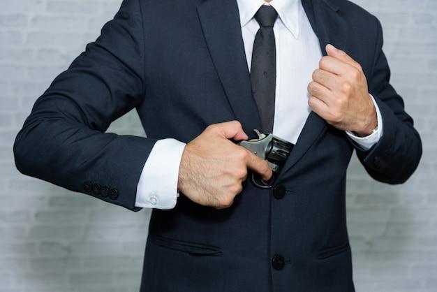 Empresario con pistola sobre fondo gris