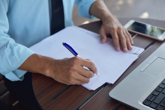 Empresario con pluma y escribir en papel