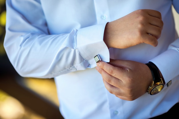 Empresario se pone gemelos. el novio se prepara en la mañana antes de la ceremonia de la boda.