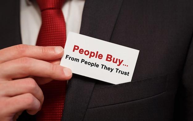 Empresario poniendo en el bolsillo una tarjeta con el texto personas compran a personas en quienes confían