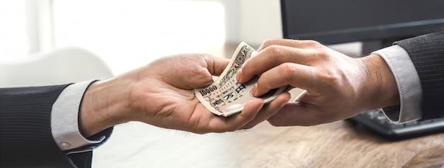 Empresario poniendo dinero en la mano de su compañero
