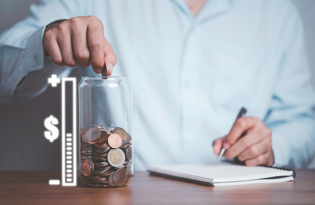 Empresario poniendo monedas y grabando en frasco de ahorro de dinero con escala virtual de cantidad de ahorro para el futuro.