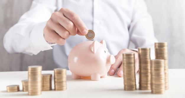 Empresario poniendo monedas en la hucha. concepto de ahorro