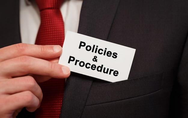 Empresario poniendo una tarjeta con políticas de texto y procedimiento en el bolsillo