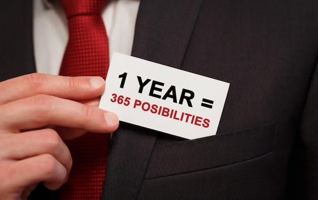 Empresario poniendo una tarjeta con texto 1 año 365 posibilidades en el bolsillo