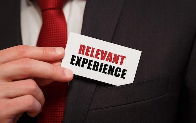 Empresario poniendo una tarjeta con texto experiencia relevante en el bolsillo