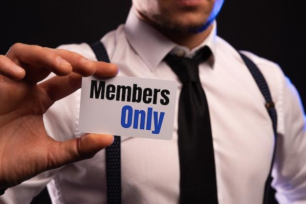 Empresario poniendo una tarjeta con texto miembros solamente en el bolsillo.