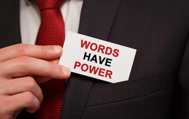 Empresario poniendo una tarjeta con texto las palabras tienen poder en el bolsillo