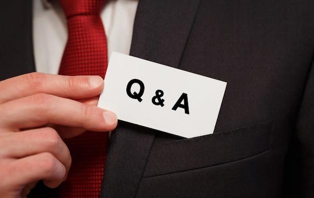 Empresario poniendo una tarjeta con texto q y a en el bolsillo