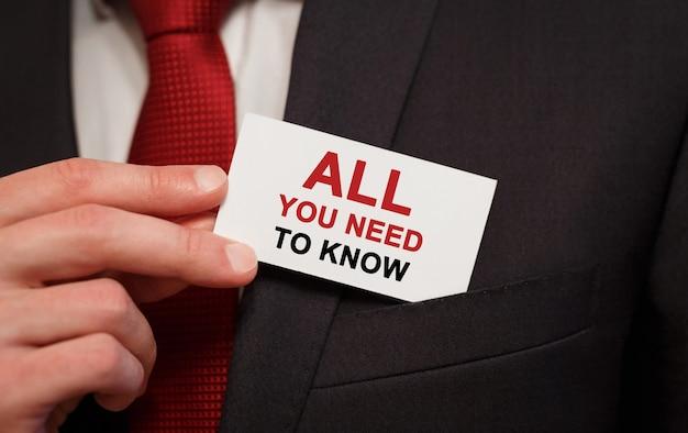 Empresario poniendo una tarjeta con texto todo lo que necesita saber en el bolsillo