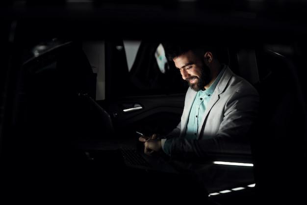 Empresario positivo terminando su trabajo horas extras trabajando hasta tarde.