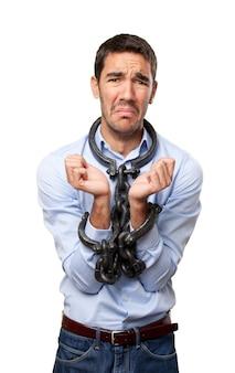 Empresario preocupado con los brazos encadenados