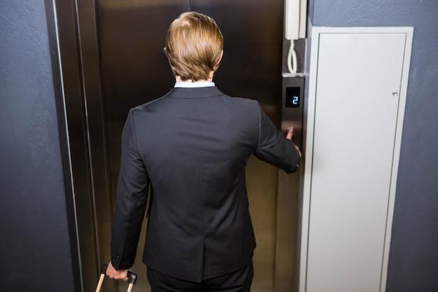 Empresario presionando el botón del elevador en la oficina
