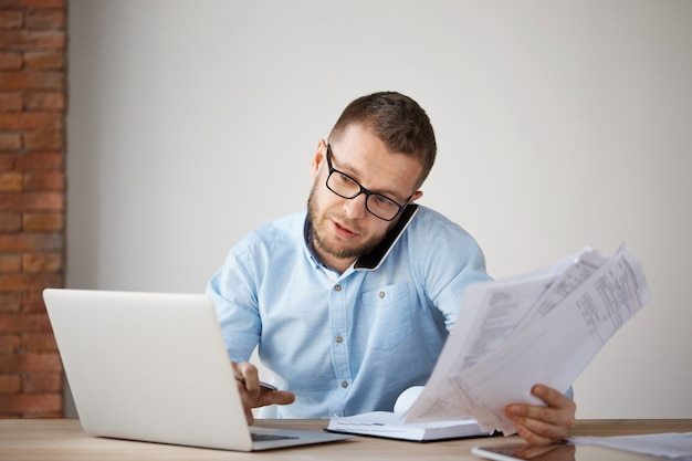 Empresario profesional serio hablando por teléfono con el cliente, sosteniendo papeles en la mano
