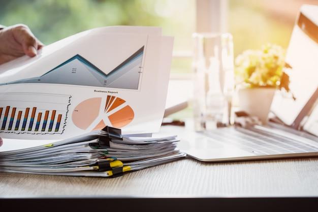 Empresario que prepara documentos de informes con gráficos, tablas en pilas de archivos de documentos para finanzas