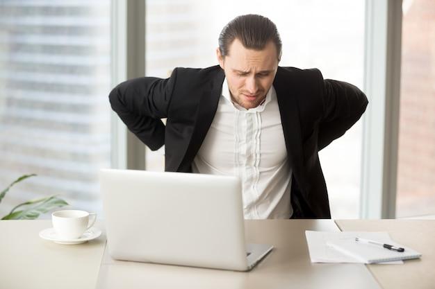 Empresario que sufre de dolor de espalda en el lugar de trabajo