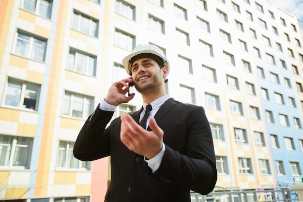 Empresario de raza mixta del medio oriente por edificio de apartamentos