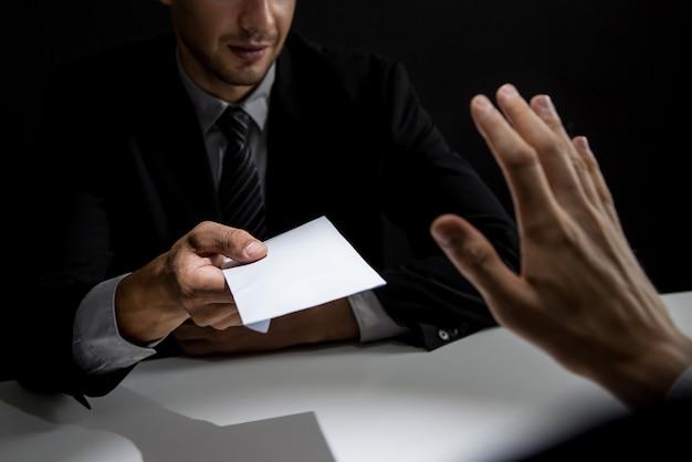 Empresario rechazando dinero en un sobre blanco ofrecido por su compañero en la sombra.