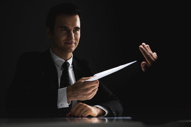 Empresario rechazando el soborno en un sobre blanco ofrecido por su compañero.