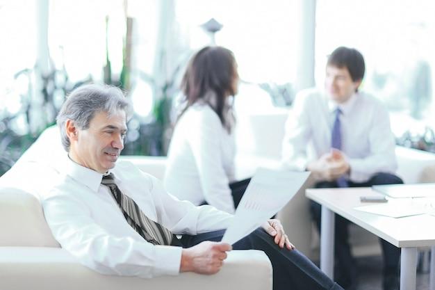 Empresario reflexionando sobre un documento sentado en una oficina moderna.foto con espacio de copia