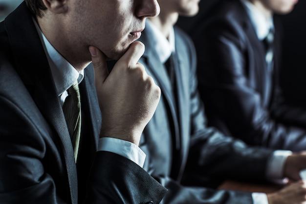 Empresario reflexivo y equipo empresarial en el lugar de trabajo