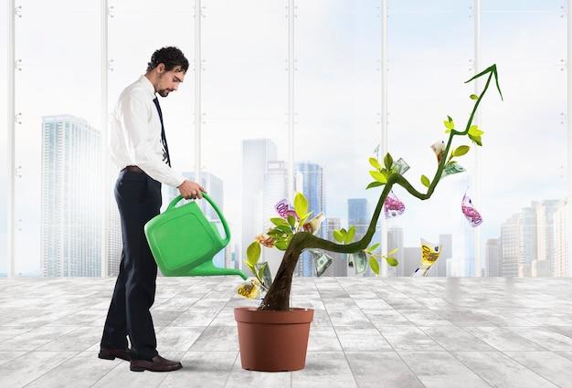 Empresario regando monedas de dinero como si fueran plantas