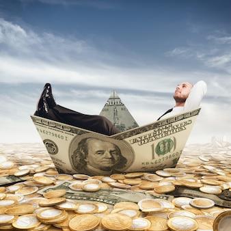 Empresario relajado en un barco de billetes