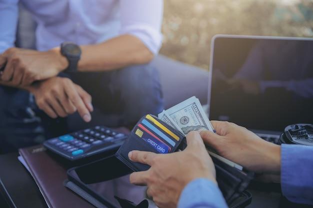 Empresario en la reunión de negocios contando y pagando dinero después de las negociaciones con los socios comerciales