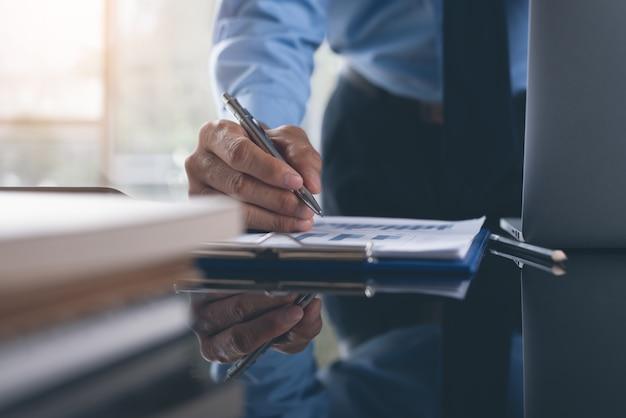 Empresario revisando informe comercial trabajando en oficina