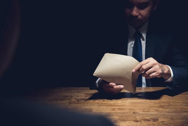 Empresario revisando el sobre dado por su compañero en cuarto oscuro