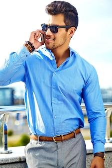 Empresario en ropa formal y gafas de sol usando su teléfono