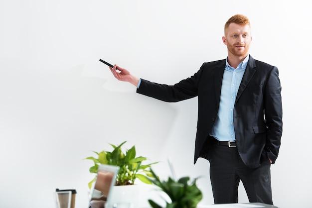 El empresario en una sala de reuniones explica algo en una reunión de formación