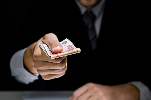 Empresario secretamente regalando dinero en la oscuridad