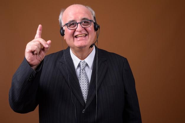 Empresario senior con sobrepeso usando anteojos contra la pared marrón