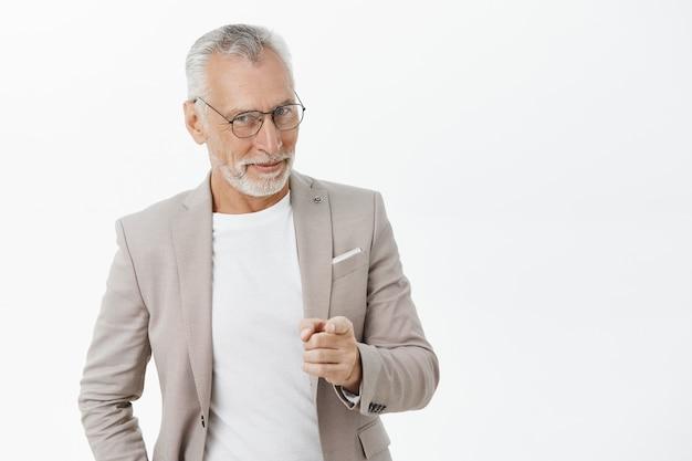 Empresario senior sonriente descarado con barba y cabello gris apuntando