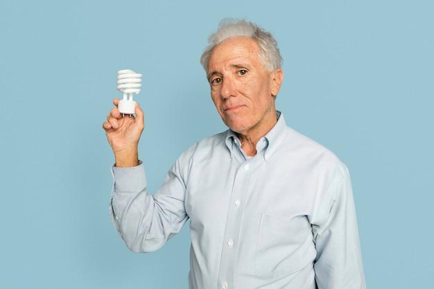 Empresario senior sosteniendo una bombilla para la campaña de innovación